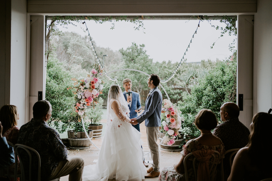 A bride and groom hold hands at their wedding. The rain is visible outside.