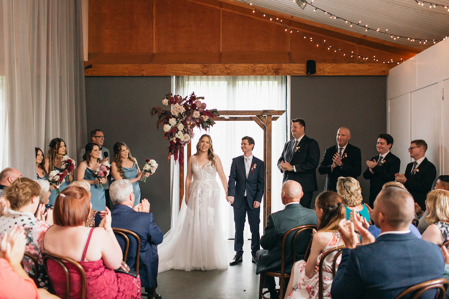 A rainy day wedding at Osteria. The bride and groom smile and hold hands in front of their guests.