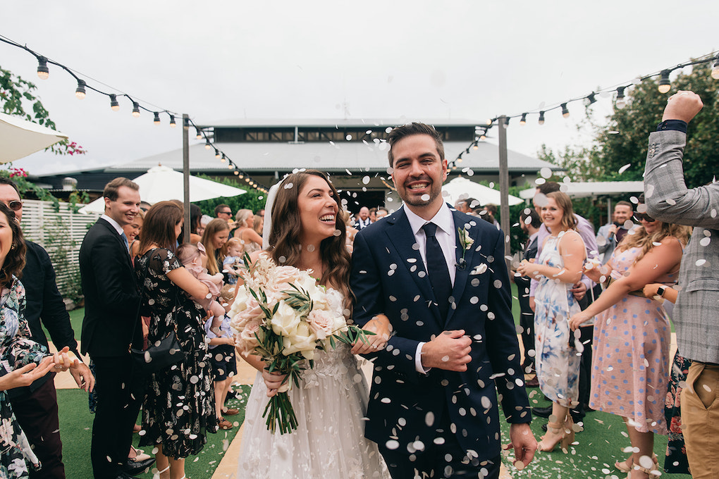Bride and groom in ceremony garden with biodegradable confetti