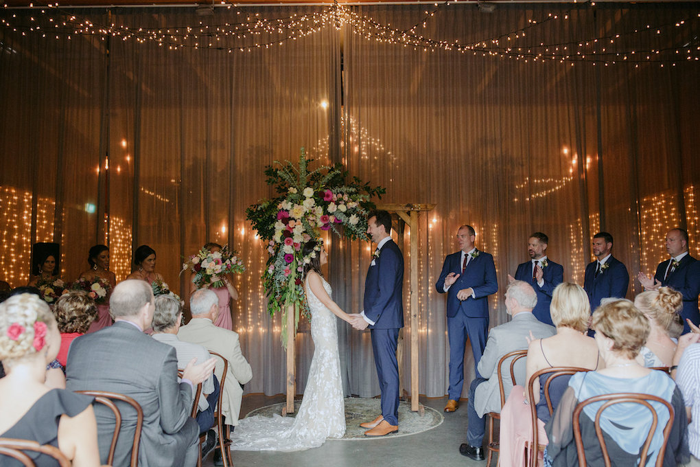 rainy wedding day indoor ceremony. A bride and groom stand in front of a floral arbour indoors.