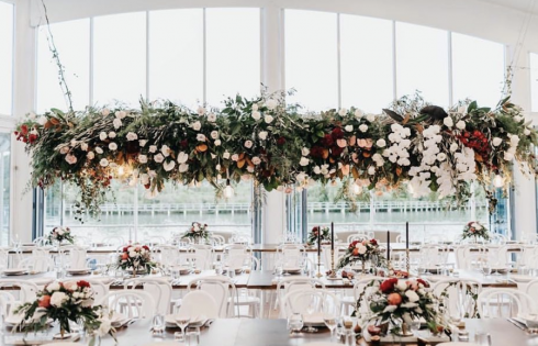 Waterfront wedding venue flowers hanging at reception