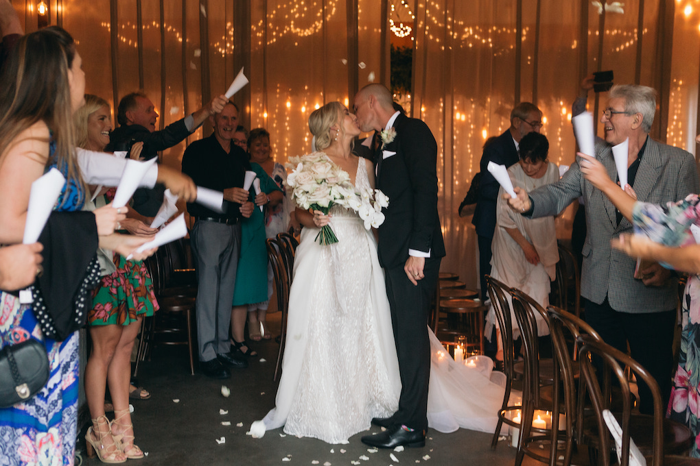 A bride and groom kiss at their rainy day wedding at Osteria Casuarina.
