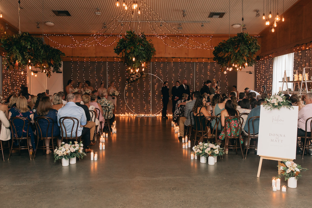 A beautiful fairy lit indoor ceremony for a rainy day wedding at Osteria.