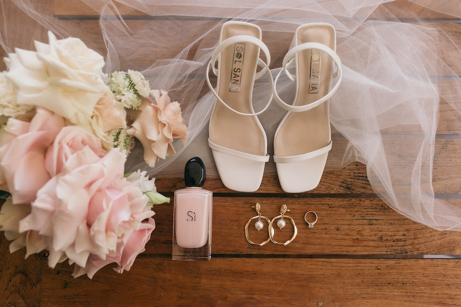 a bouquet, white high hells and a bottle of perfume on a wooden background