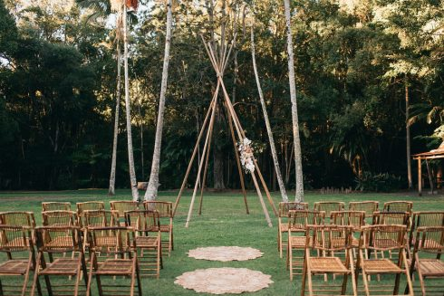 Open air lawn wedding ceremony with tipi arbour