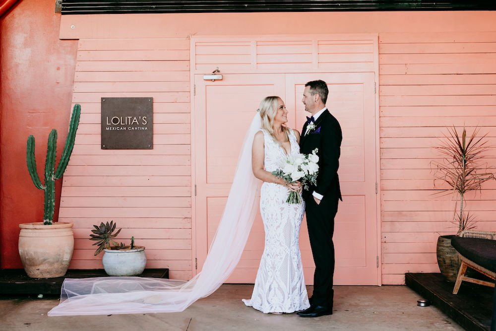 Bride and Groom in front of peach doors at lolita's mexican cantina
