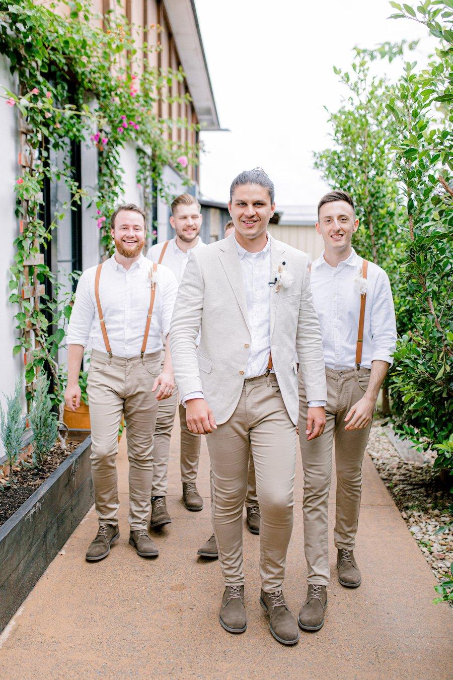 groom and groomsmen walking in osteria weddings garden