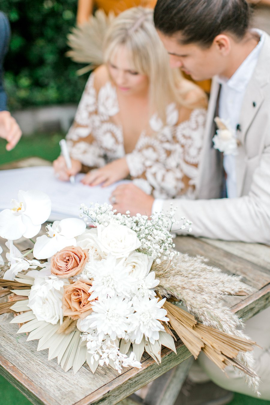 bride and groom signing at wedding ceremony
