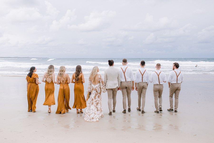 bridal party walking towards water on casuarina beach