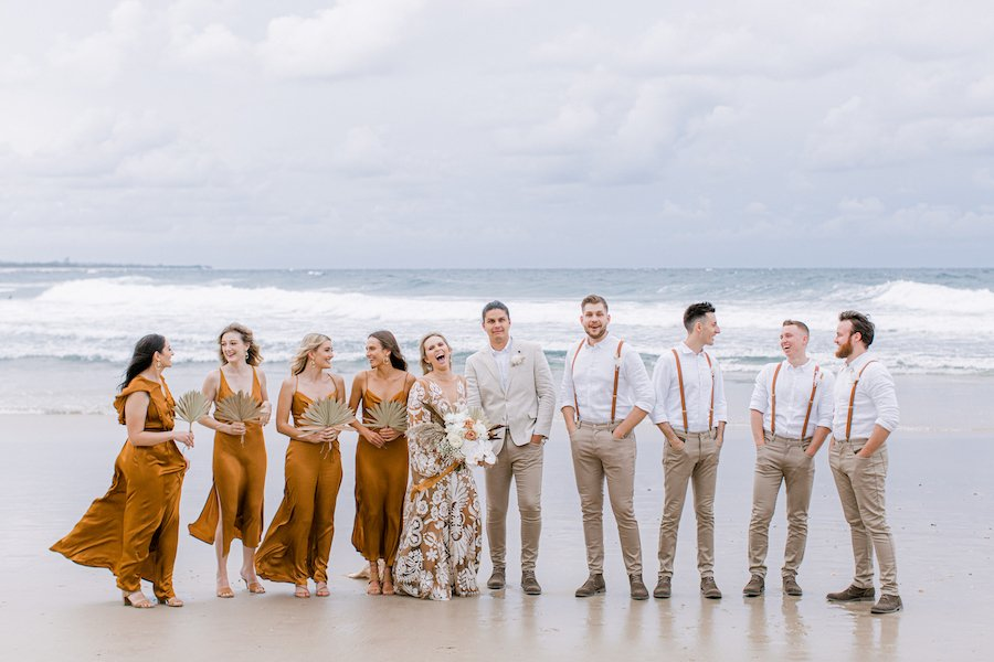 bridal party laughing on the sand at casuarina beach
