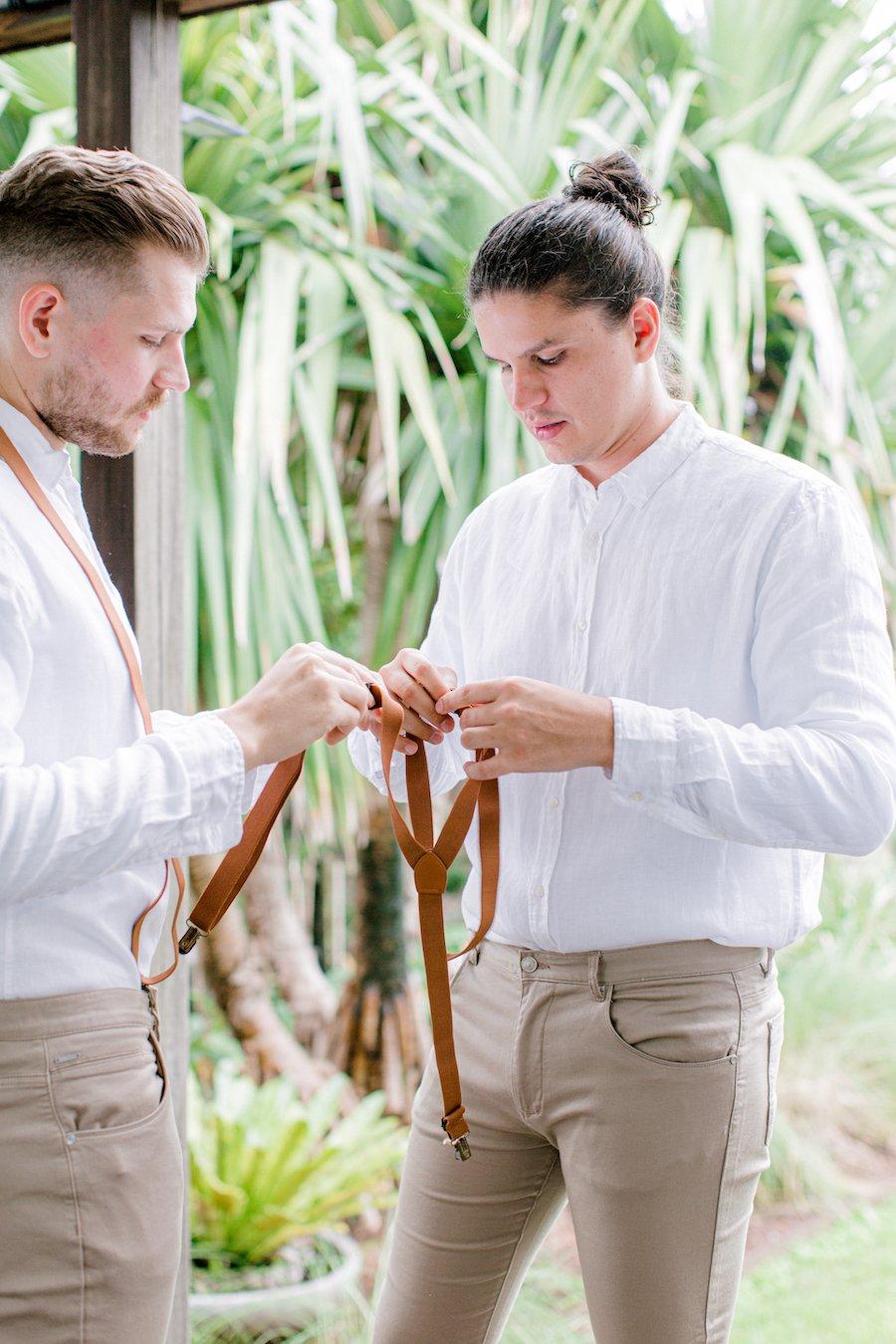 groom and groomsman getting dressed