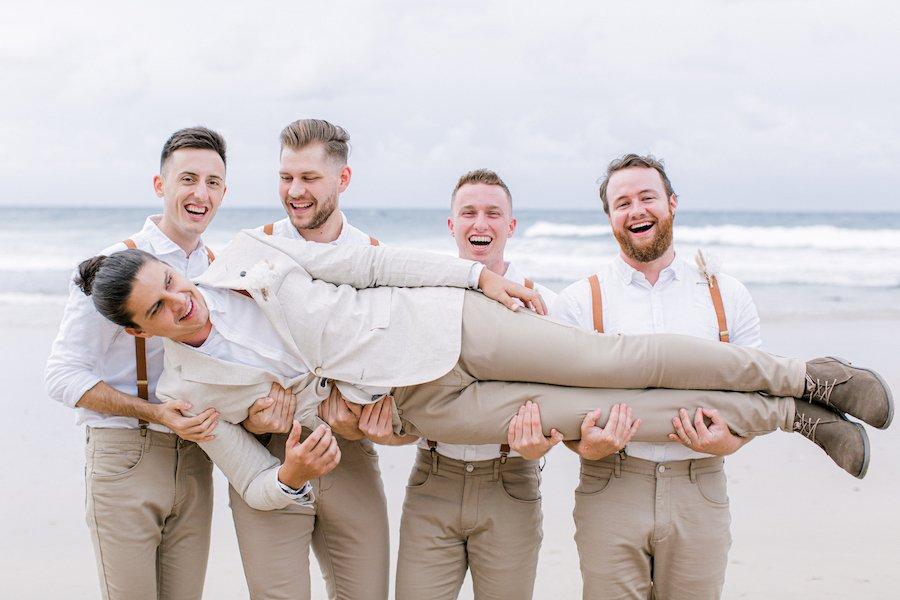 groomens carrying groom on beach