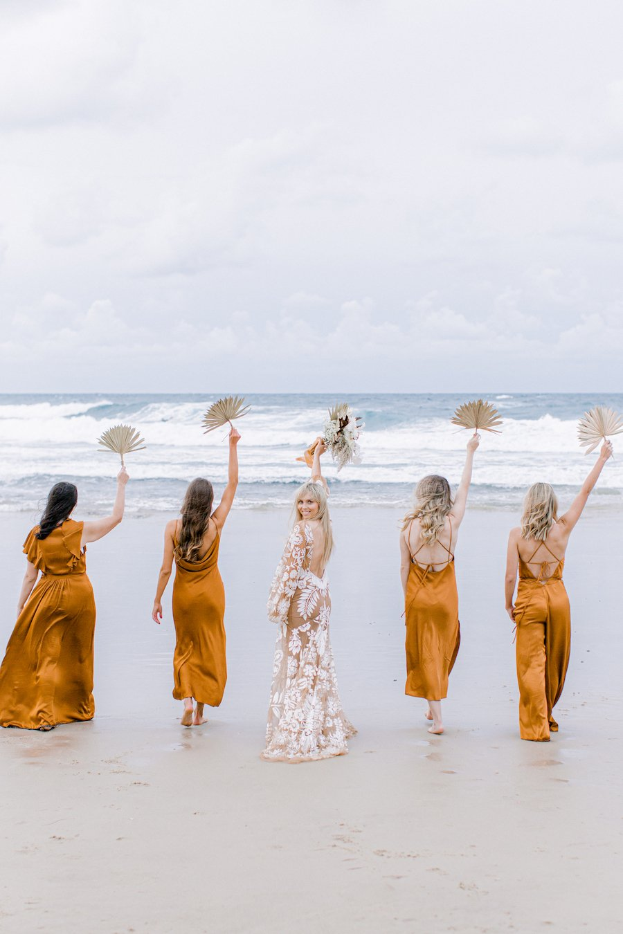 bride and bridesmaid walking on beach holding bouquets