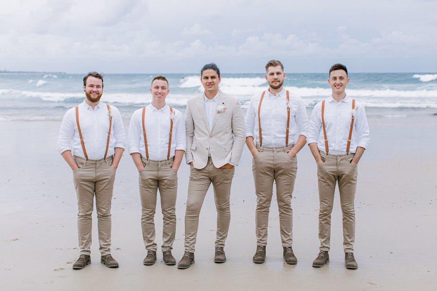 groom and groomsmen standing on beach