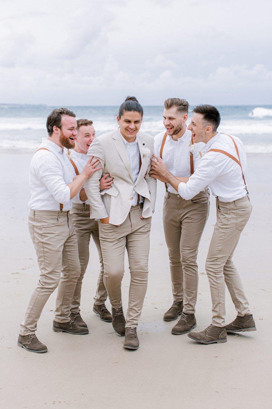 groom and groomsmen laughing on beach