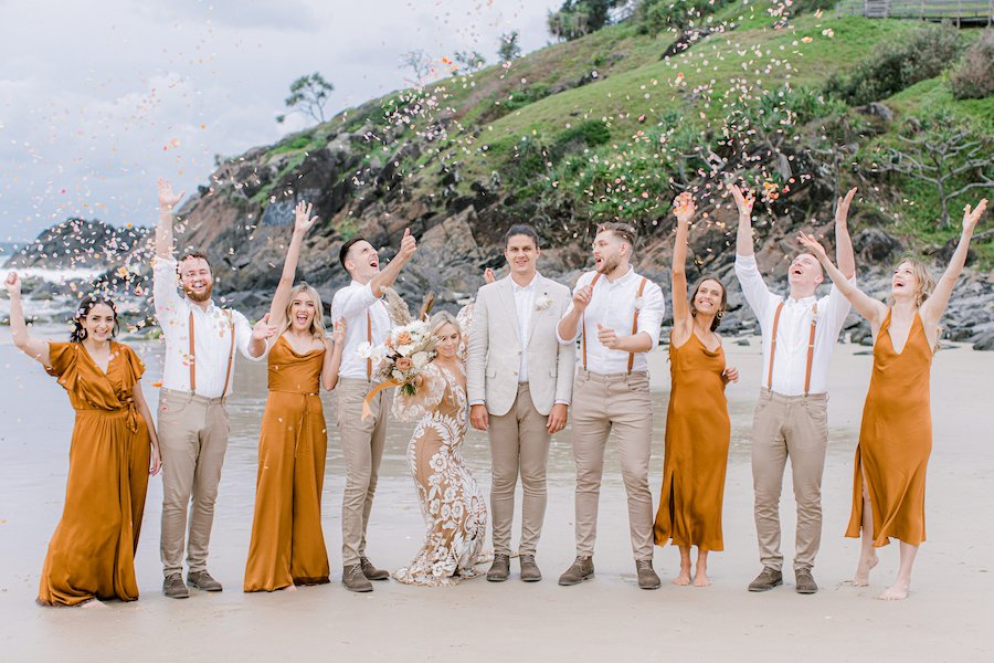 bridal party throwing the whole bride confetti on beach