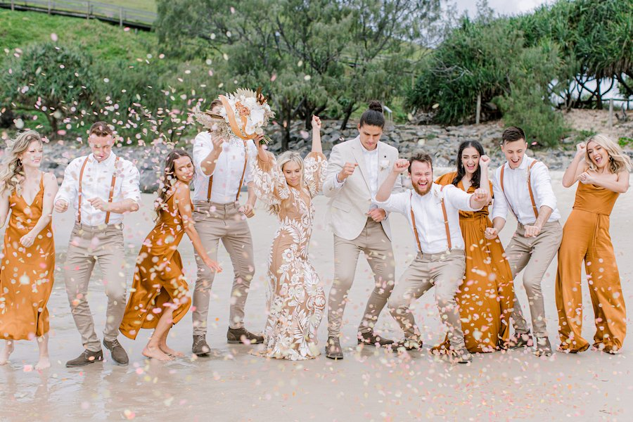 bridal party throwing biodegradable confetti on beach