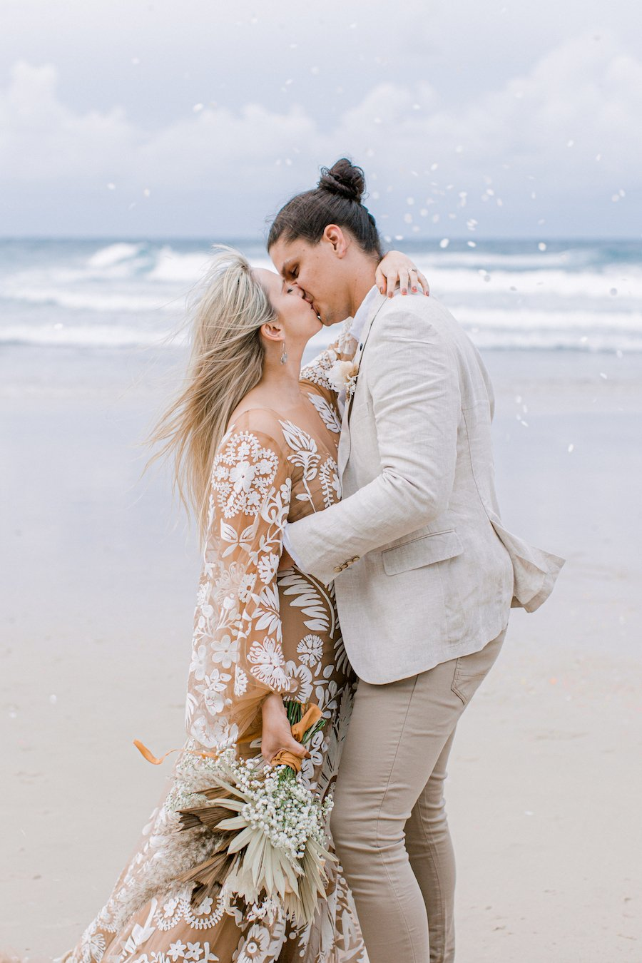 bride and groom kissing on beach with confetti