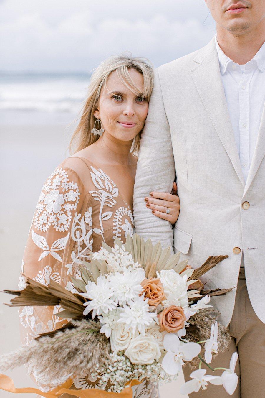 bride and groom on beach cuddling