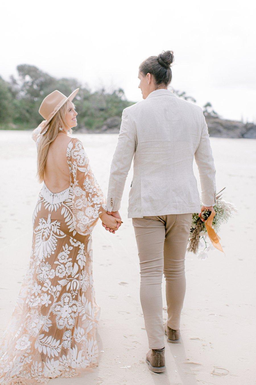 bride wearing hat walking on beach with groom