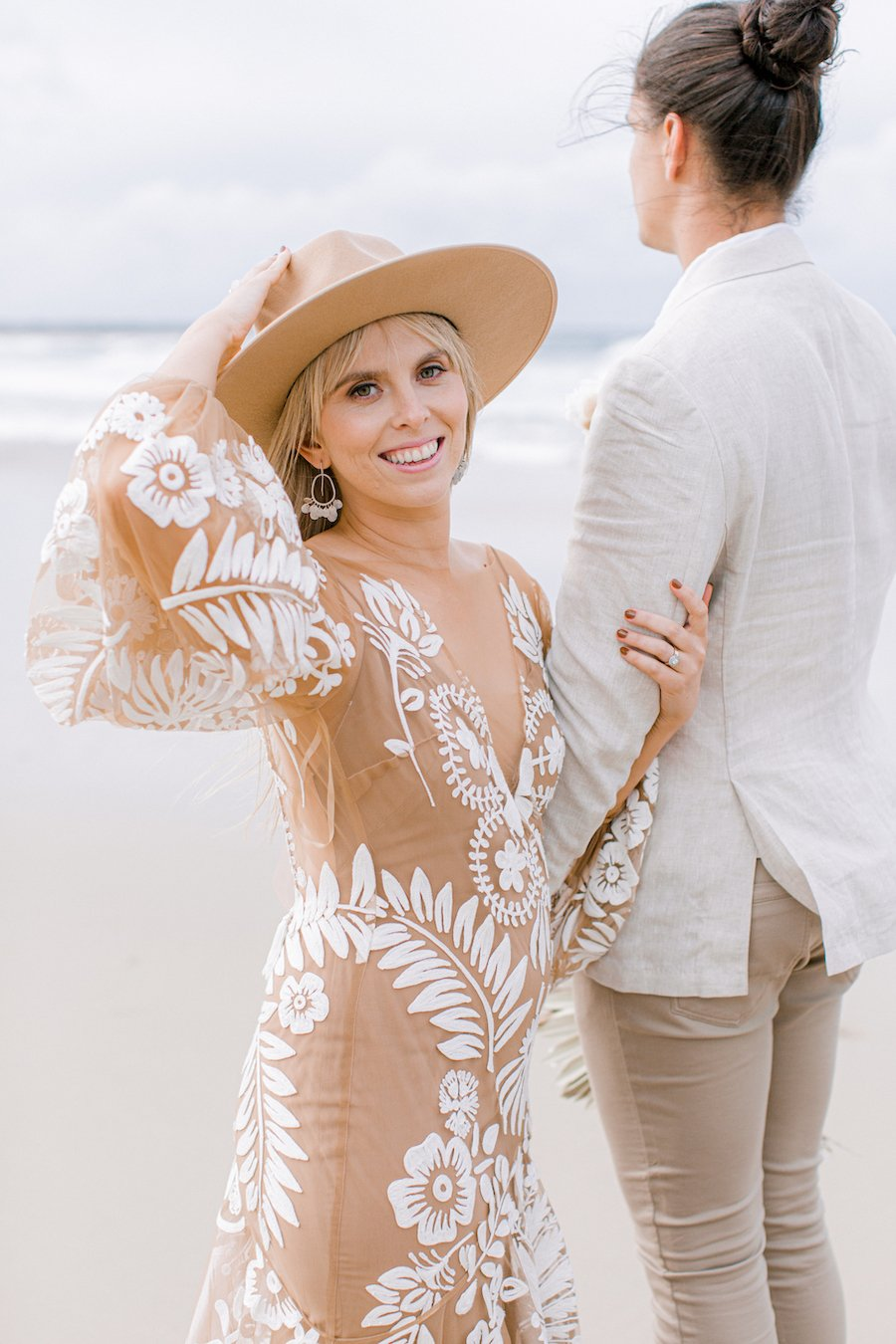 bride wearing lack of color cream hat with groom