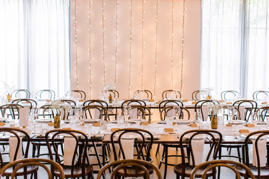 white wedding reception room with tables and chairs set up