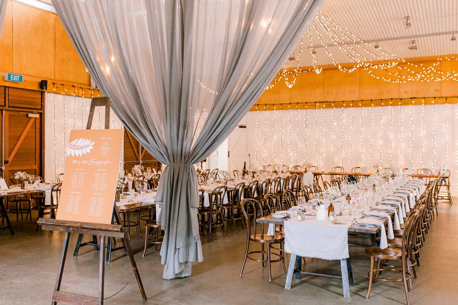 wedding reception room styled with curtains and fairy lights